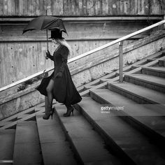 Woman walking down concrete stairs with a broken umbrella and a top hat.