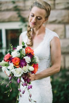 bouquet with white and orange roses, lilies, and cascading purple flowers