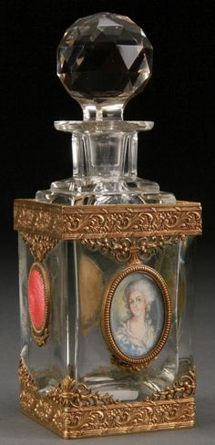 A VERY FINE CRYSTAL GILT BRONZE GUILLOCHE AND IVORY PORTRAIT MOUNTED DRESSER BOTTLE, LATE 19TH CENTURY. Attributed to Baccarat. Of square cut panel form with ornate tooled bronze mounts, three guilloche translucent rose colored enamel medallions and a hand painted ivory portrait, probably of Marie Antoinette. Bronze base stamped France. Height 7 inches (17.5 cm).