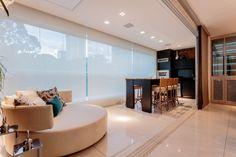 Projetado pelo escritório Morávia Arquitetura & Interiores, a varanda gourmet tem uma mesa para refeições com banquinhos altos e ar descontraído. Uma grande chaise ajuda a criar um espaço acolhedor para receber amigos