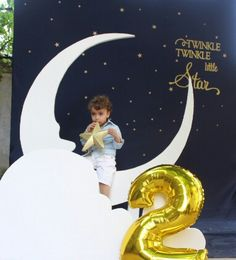 2.year boy birthday party; Moon PhotoBooth ; Cute photo idea...navy blue sheet background with stars, a bench to sit on, a big white moon made of styrofoam ; moon and star photo prop ; Gold + Glitter + Star themed birthday party ; twinkle twinkle little start party theme