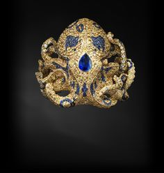 The octopus bracelet by Jack du Rose, set in yellow good with diamonds, sapphires and black opal.
