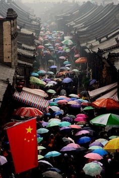 Great shot - highlights the disparity between the dreary buildings and the cheerful umbrellas. And the Coke umbrella sits right above the Chinese flag.