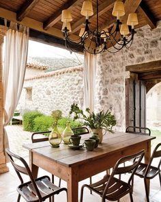 lovely combination of wood ceiling matching wood table and black chairs with beautiful stone wall!! curtains add a nice touch as well, when having a special dinner you could pull them for privacy! -V