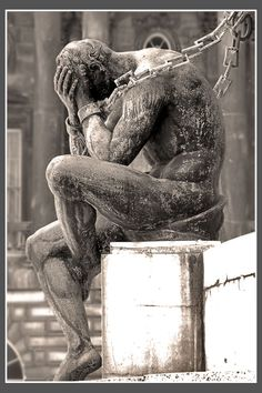 Chained male nude, part of a four- or five-figure stone sculpture in Liverpool, England.  Photo by Croxie, 2006.