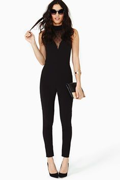 Super chic black jumpsuit featuring a high neckline and dotted sheer mesh detailing. Split back with button and zip closures. Stretch fabric, unlined. Perfect paired with bold lips and platform pumps! By N