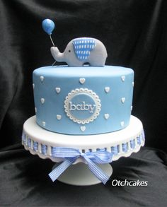 Elephant baby shower cake for a boy. Blue fondant cake with white heart polka dots. Elephant has a plaid ear to match the ribbon. Cake by https://www.facebook.com/Otchcakes