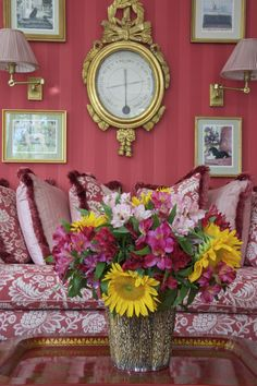 two-toned striped pink wallpaper with bold pink and white print sofa and gold accents: charming--Carolyne Roehm Interior