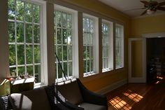 Wall of Marvin windows in this beautiful sunroom of this raised home.  Great view of the treetops!