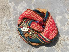 Kinship Stories: Tribal brooch made with vintage fabric from the hilltribes of Thailand and two brass Turkmen beads. This piece is entirely handmade and one-of-a-kind.