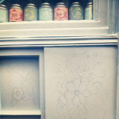 Drawing out the flowers and macarons on the shop front.