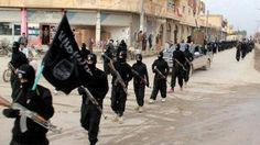 This image posted on a militant website in 2014 shows fighters from ISIS group, marching in Raqqa, Syria.