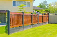 Modern lattice fence comprised of black stained wood posts and base, with lighter red toned body.