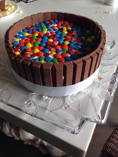 A cool birthday cake with a KitKat fence and scattered m&ms...