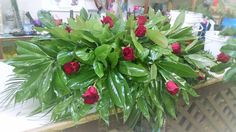 Mixed greenery magnolia and pine accented with red roses.