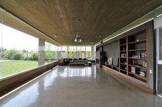 salón amplio con pared de hormigón y estanterías de madera