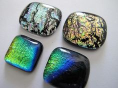 Four colourful freeform, handmade Dichroic glass cabochons, for Jewellery making, Stained glass etc.  The larger square rainbow, black backed cab is about 23mm x 21mm.  The smaller square rainbow, black backed cab is about 20mm x 19mm.  The square metallic pink/gold /green, black backed cab is about 23mm x 26mm.  The square metallic silver/grey/pink, black backed cab is about 23mm x 27mm.   They are best suited for custom bezel cups and settings, wire wrapping and wrapping...