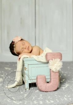 Newborn baby girl in planter with first initial for birth announcement. Shabby chic. Blue and pink.