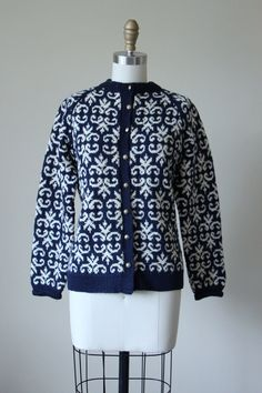 ♛The Details  Beautiful hand-knit ca. 1940s/1950s cardigan of pure wool in a Celtic-style pattern of navy and ivory.  •closes with decorative etched metal buttons of silver •warmth without weight  Designer label is not found -- this is hand-knit.  All accessories (belts, jewelry, crinolines, pins, etc.) are for style inspiration only unless indicated.  ♛The Measurements  About a modern size S to M, or could fit smaller frames loosely  Bust (underarm area measured flat, then doubled) 40…