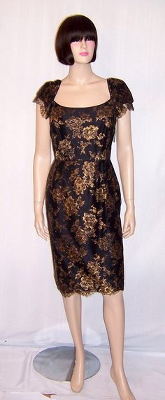 This is a luxurious and timeless black cocktail dress with capped sleeves and rich, gold metallic embroidered flowers on fine black net, designed by Darby Scott. The dress is unworn, and has its original tag still attached. Darby Scott is a distinctive American fashion designer known for her impeccable craftsmanship and her use of opulent and luxe fabrics. This striking cocktail dress is of the 1990s vintage, is in excellent condition, and would be equivalent to a Size 4 to Size 6.