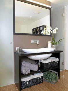 Baderommet er i åpen løsning med soverommet. Arealet er derfor delt inn i tre soner, med dusj til høyre og toalett til venstre. De har fått like store avlukker bak to dører i frostet glass.