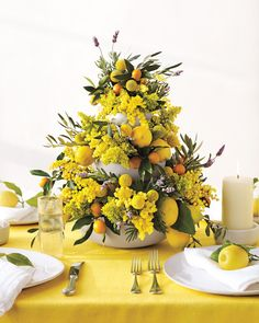 For a bold and cheery statement piece, fill tiered bowls with dense tufts of goldenrod, fuzzy clusters of mimosa, globelike craspedia balls, olive leaves, kumquats, lemons, and sprigs of fresh lavender.