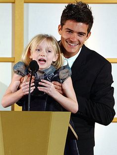 Orlando Bloom holds Dakota Fanning up so she can give a thank you speech after receiving her award....CUTEST THING EVER