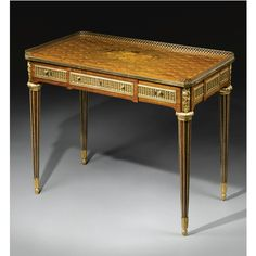 A highly important gilt-bronze-mounted kingwood, sycamore, amaranth, marquetry and parquetry writing table stamped J.H. Riesener Louis XVI, circa 1780 the three-quarter gallery cast with ovoloes above a rectangular top richly inlaid with a central oval marquetry panel depicting a bouquet of flowers contained within a trelliswork ground enclosing flowerheads, the panelled frieze with an alternating band of husks and lunettes containing three drawers,