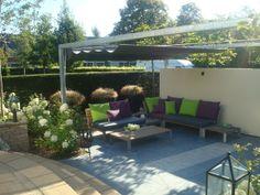 Modern loungeterras met flexibele overkapping en fraaie muur. #www.hoofthoveniers.nl