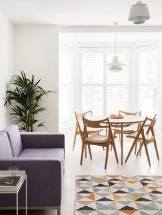 Der Essbereich ist in den größeren offenen Raum in der Mitte des Hauses. Hier sehen wir, wie Elemente wie das natürliche Holz, Restaurants, Set, zeitgenössische lila Sofa und bunten Teppich Textur und Abwechslung in das weiße Feld anbieten.