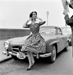 Model poses on Mercedes-Benz 190SL roadster in floral-print summer dress with white pique collar and cuffs, Italy, 1955