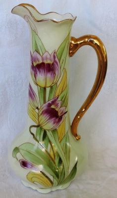 This lovely Limoges pitcher/ewer measures 12 high. It features hand painted tulips and gold trim. The bottom is marked McCarthy France Studio Chicago D C France. It is in excellent condition, havin