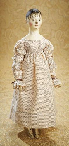 """Very Fine Early 19th Century Wooden Doll.17"""". Wood head & torso w molded bosom & carved bodice edge, brown hair painted smoothly over the crown w wisps of curls around forehead, sculpted ears, painted brown eyes, aquiline nose, closed mouth, dowel-jointing at the shoulders, elbows, hips & knees, beautifully-shaped hands, shapely calves w tiny ankles & slender feet, painted shoes, & high-waist cotton dress. Early 19th century."""
