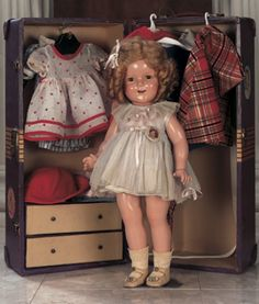 """Shirley Temple with Trunk and Wardrobe 18"""" (46 cm.) Composition socket head,green sleep eyes,painted lashes and brows,real lashes,open mouth,six teeth,blonde mohair wig in ringlet curls,five piece composition body. Condition: generally excellent,slight costume dust. Marks: Cop. Ideal N&T Co. Shirley Temple (head) Shirley Temple 18 (torso). Comments: Ideal,circa 1935. Value Points: the child film star wears her original tagged green pleated party dress,and owns an original Shirley Temple…"""