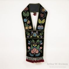 What a striking Ojibwe bandelier bag! This shoulder bag worn with strap resting on one shoulder and worn across the body has colorfully beaded floral designs on a rich black velvet which is edged in o