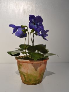 Violet.  Porcelain Flowers, and pot.  Tole leaves and stems.  Approximately 6 1/2 x 4.