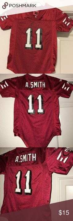 """TODDLER SF 49ers Alex smith jersey romper Sz: 18M for sale is a toddler, Reebok brand, red, SF 49ers, Alex Smith jersey.  Overall the jersey is in good condition, there is a small black oval on the chest that shows the letters SF, the SF has peeled away over the years. it snaps at the bottom, missing one of the snaps.   Sz: 18M  If you have any questions or would like additional photos please feel free to ask  From under one arm to under the other measures appx 11"""" from the top of the…"""