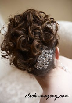 This wavy upo is held in place with a broach. Found it on weddingtresses.com