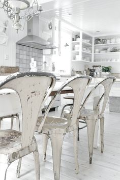 white kitchen * white wooden diningroom table * white rustic metal chairs * white floor