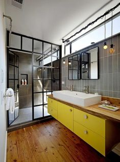 I LOVE the window look of the shower. Love the yellow cabinets with the medium wood and accents too.