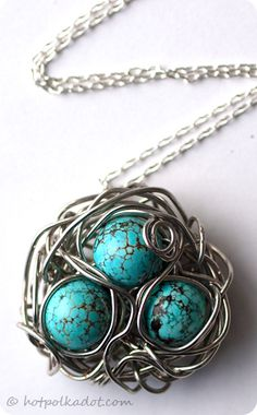 bird's nest necklace made of twisted silver wire and shiny turquoise beads on a dainty cable chain