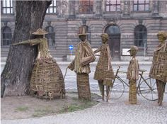 """Artists Agnieszka Gradzik and Wiktor Szostalo use the organic material to create wicker-people that embrace the tree. 2008 UN Conference on Climate Change in Poland. Exhibit entitled """"Lonely Tree, Lonely People."""""""