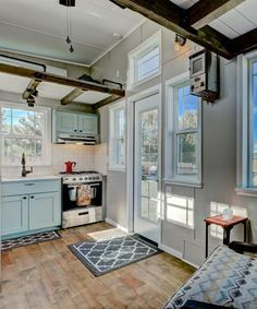 "This 22' custom tiny house on wheels features 5"" hickory hardwood flooring. Large windows throughout the house allow for ample natural light.  Love the exposed members of the lofts."