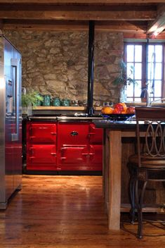 Beautiful Rustic Kitchen with a Red AGA stove against that stone wall is stunning.