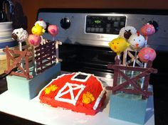 Barn cake with farm animal cake pops in popsicle stick corrals.