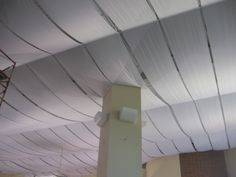 Fabric curls on ceiling.