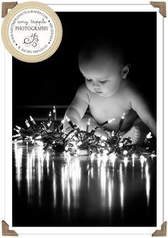"Christmas Baby Photo … the trick is not to do it in full darkness. Get the room dark enough to see the lights well and set up a ""bounce card""…we used a white ""presentation"" board…one of those fold out white cardboard paper things that's about 4×6? Put that next to the baby but out of frame and it will bounce light back onto the baby. 