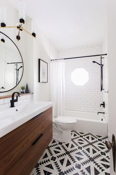 Graphic, geometric patterned floor tile serves as the focal point and color palette inspiration for this bathroom. Wooden, flat panel vanity drawers bring a natural, warm element to the black and white space. Since an octagonal shower window is the only source of natural light, white walls and subway tile help brighten the room.