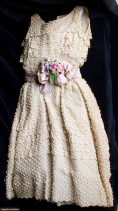 Christian Dior Couture Gown, Spring 1955 in Cream organdy embroidered all over in tiny raised sprigs, fitted, sleeveless bodice & fully gathered skirt, mauve silk belt over aqua leather, Centre Front bow & cloth flower bouquet.