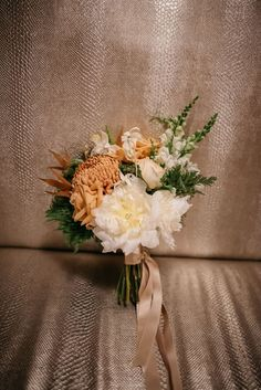 Uniquely beautiful fall bridal bouquet: white peonies, cinnamon peach roses, white snapdragons, spicy chrysanthemum, and ferns | Hip Autumn Wedding at Alden Castle in Brookline, MA | Photographer: Love and Perry
